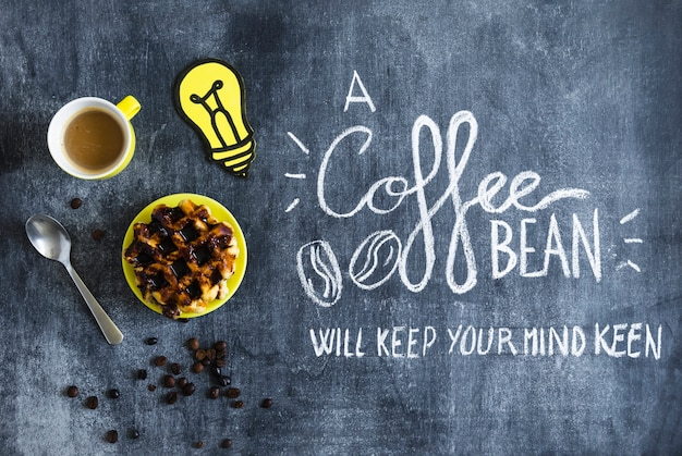 Waffles with chocolate; coffee cup and paper cutout light bulb with text on chalkboard
