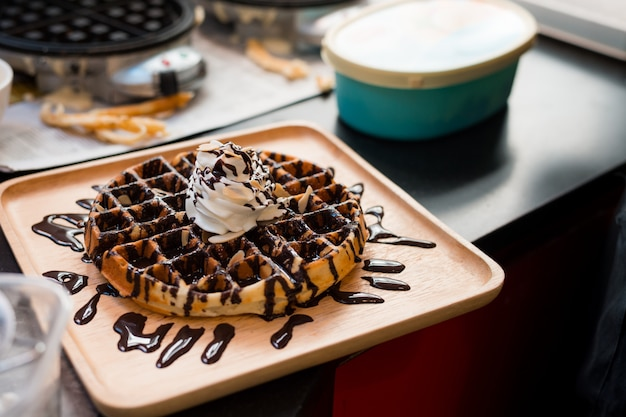 Waffles with chocolate sauce on wooden plate