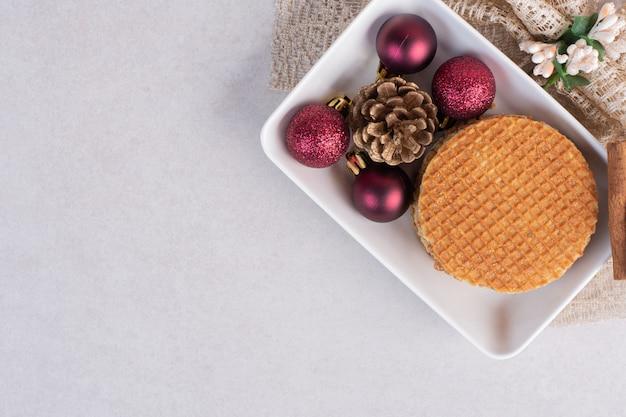 흰색 접시에 계 피와 크리스마스 장난감 와플