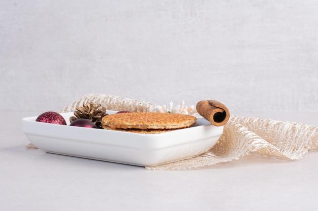 Cialde con cannella e giocattoli di natale sul piatto bianco.