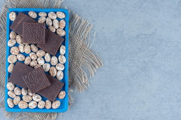 Вафли с кондитерскими изделиями с корицей на деревянном подносе, на мраморном столе.