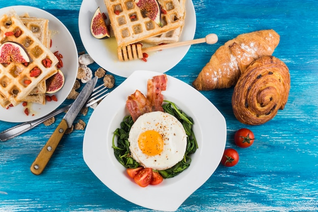 Waffles with fig; baked pastries and egg fried egg on white plates over blue textured backdrop