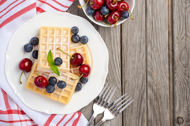 Waffles with fresh cherries and blueberries on a rustic wooden table