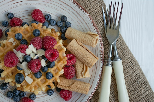 Waffles with fresh fruit for breakfast. sunny waffles. white wooden background.