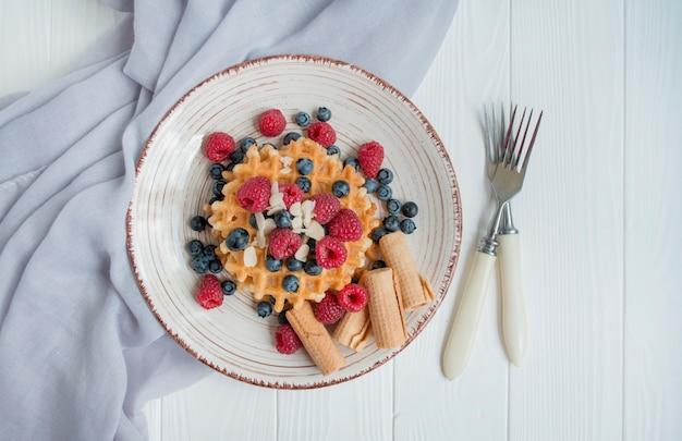 아침에 신선한 나무 딸기, 블루 베리와 와플. 벨기에 와플. 밝은 나무 배경. 프리미엄 사진