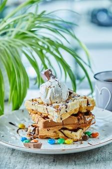 홍차와 함께 흰 접시에 아이스크림, 초콜릿, 초콜릿 볼 와플