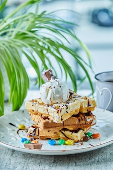 Waffles with ice-cream, chocolate, chocolate balls on the white plate with tea