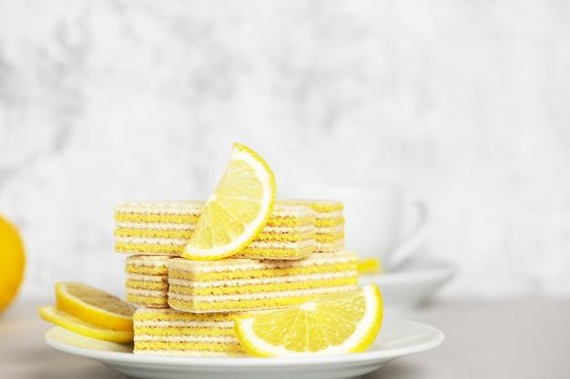 レモンとミルクを詰めたワッフル。ぼやけた背景の受け皿に横たわっているレモンスライス。美味しくて甘いデザート。パンファイト。スペースをコピーします。ティータイムのコンセプト。