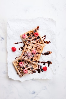 Waffles with raspberries and chocolate syrup