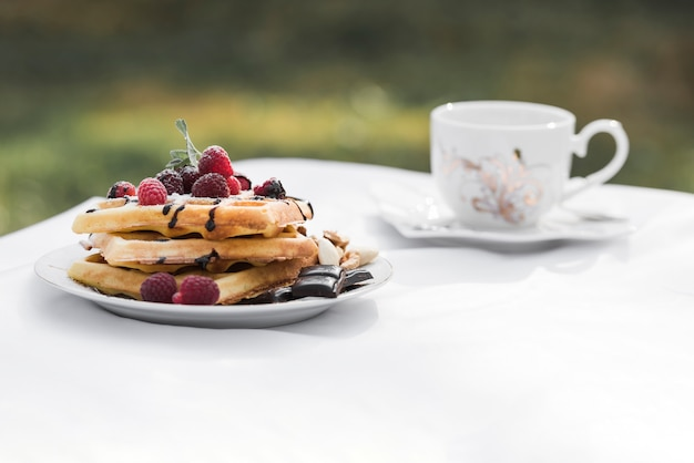 Waffles with raspberries toppings on plate and ceramic coffee on white table at outdoors