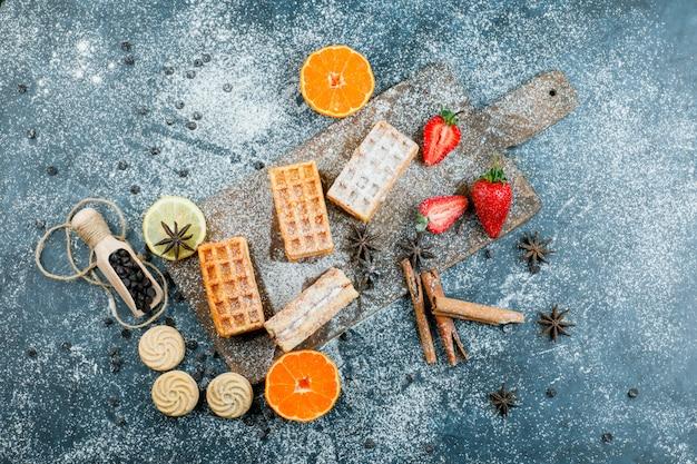 ワッフル、スパイス、クッキー、チョコチップ、フルーツの上面図、汚れたまな板の表面