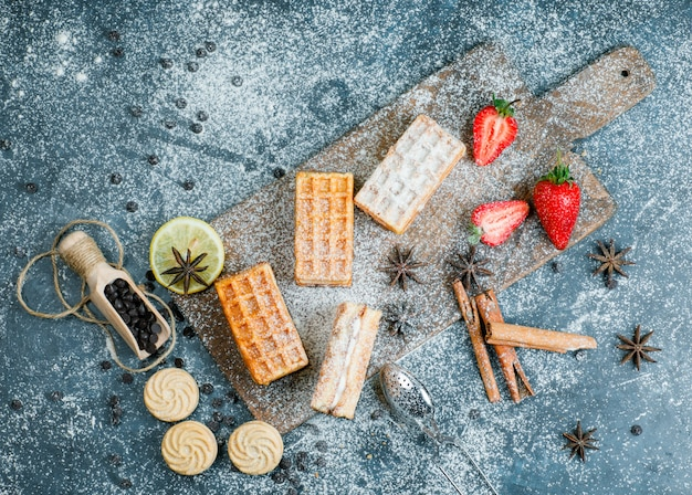 Waffles with spices, cookies, choco chips, strawberry, strainer flat lay on grungy and cutting board surface