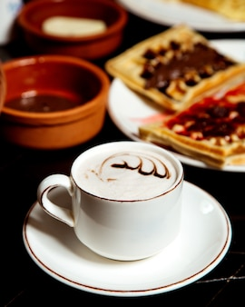 Waffles with syrup and cappuccino