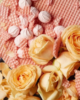 Для украшения использовали вафли, зефиры и оранжевые розы. концепция дня святого валентина. крупный план оранжевых роз с красивыми лепестками.