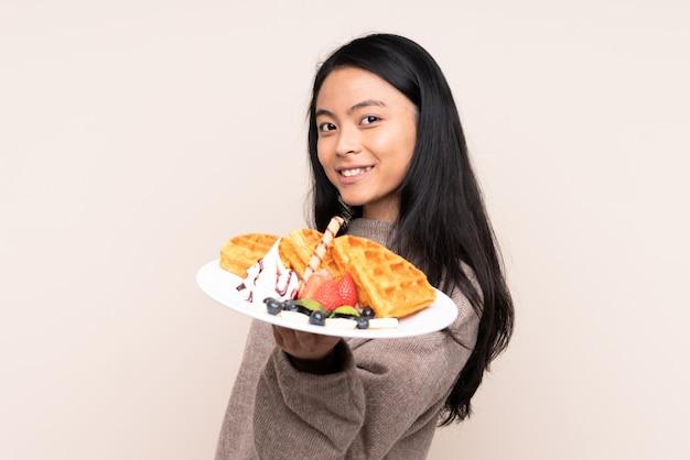 Девушка подростка азиатская держа waffles изолированный на бежевой предпосылке с счастливым выражением