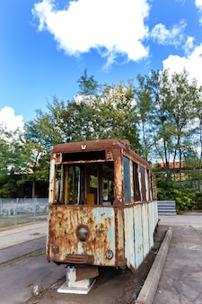 Wagon of old rusty destroyed tram outdoors at sunny day.