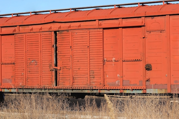 A wagon of an old rusty freight train stands on the rails on the front line sprouted dry vegetation