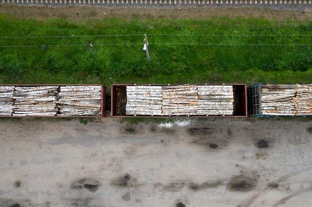 Вагоны с деревянными и березовыми бревнами сверху.