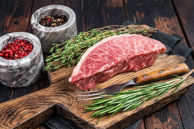 Wagyu a5 생 등심 또는 등심 스테이크, 도살 판에 고베 쇠고기 고기. 어두운 나무 배경입니다. 평면도.