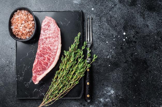 와규 생 등심 스테이크, 대리석 판에 고베 쇠고기 고기. 검은 배경. 평면도. 공간을 복사합니다.