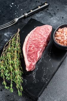 와규 생 등심 스테이크, 대리석 판에 고베 쇠고기 고기. 검은 배경. 평면도.