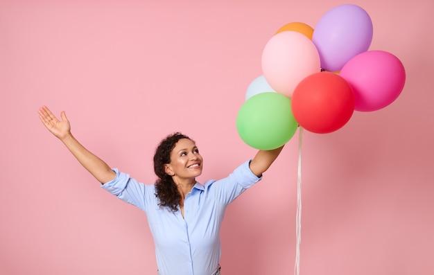 陽気な陽気な幸せな笑顔と歯を見せる笑顔のウエストの長さのportarit腕を上げて、コピースペースでピンクの背景に分離されたカラフルな気球を見て美しい巻き毛の髪の女性