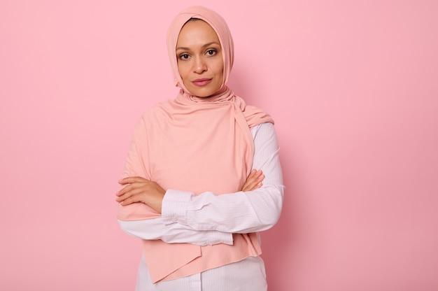 ピンクのヒジャーブのゴージャスなアラビアのイスラム教徒の女性の腰の長さの肖像画は、コピースペースとピンクの背景に、魅力的な視線、自信を持って見える、交差した腕でカメラを探してポーズをとる