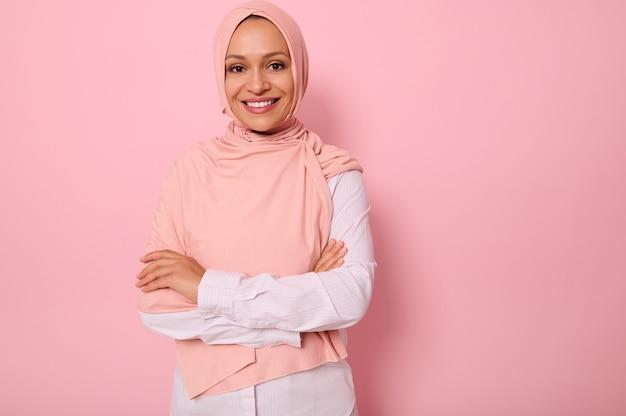 ピンクのヒジャーブのゴージャスなアラビアのイスラム教徒の女性の腰の長さの肖像画は、コピースペースとピンクの背景に、魅力的な視線、歯を見せる笑顔、自信を持って見えると交差した腕でカメラを探してポーズをとる