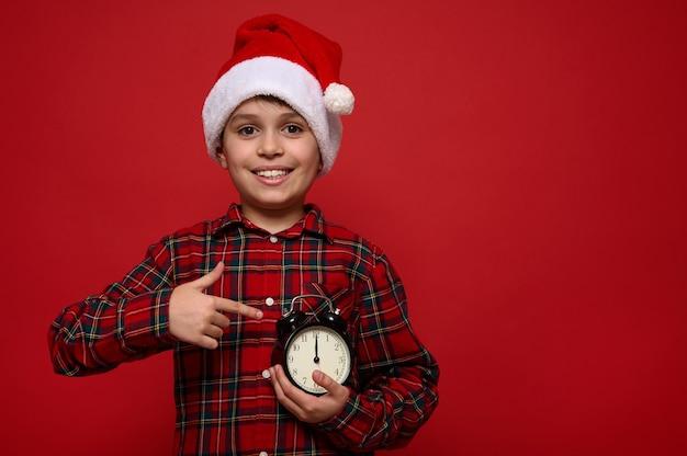 До пояса портрет очаровательного мальчика с красивой зубастой улыбкой, в шляпе санты и показывающего время на циферблате черного будильника в его руках. сейчас полночь. с рождеством христовым концепция