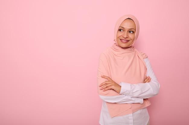 魅力的な若いアラブのイスラム教徒のかなりゴージャスな女性の腰の長さの肖像画は、コピースペースと思慮深く笑っているピンクの背景の側面を不思議に見ているヒジャーブの頭を覆っています