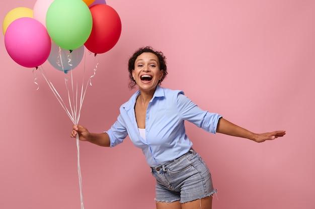 笑って、陽気で、カラフルな風船を持って、カメラを見て、広告用のコピースペースで明るいピンクの背景にポーズをとって、美しいアフリカ系アメリカ人の若い女性の腰の長さのビュー