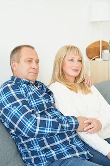 Портрет талии зрелой пары в домашнем интерьере на софе. красивый мужчина и женщина среднего возраста