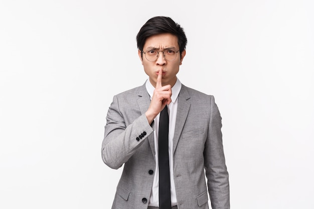 Waist-up of angry and disappointed young asian office manager, employer shushing at person being rude, talking too loud, prohibit to say something, tell shut up, quiet please, place finger on lips
