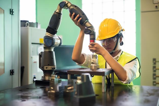 안전모와 보호 안경을 쓴 아시아 기술자 엔지니어가 제조 공장에서 자동화 로봇 밀링 암을 확인합니다. 안전 업무 프로세스의 품질 관리(qc).