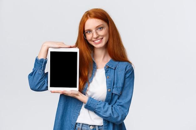 빨간 머리, 안경을 쓴 파란 눈, 응용 프로그램 소개, 새 앱 발표, 디지털 태블릿을 들고 가제트 디스플레이를 보여주고 미소 짓고 다운로드를 권장하는 허리 위로 매력적인 자신감 있는 여성.