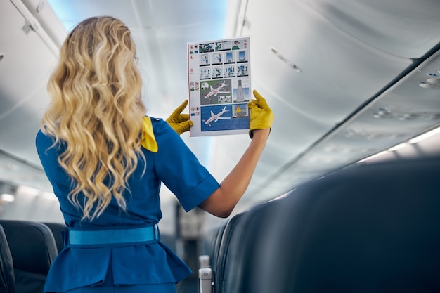 Waist up back view portrait of blonde stewardess showing airplane safety memo in the salon of civil aircraft