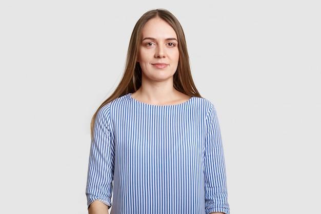Талия брюнетка европейка с длинными темными волосами, макияж, здоровая кожа, носит полосатую синюю блузку, позирует на белом. концепция красоты и женственности