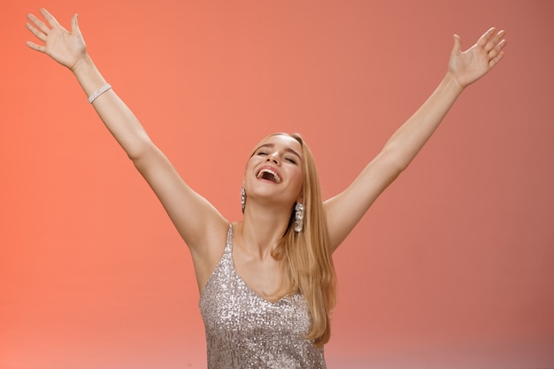 Waist-up carefree happy girl fulfill dream raising hands up sky joyfully close eyes smiling celebrating good perfect news triumphing achieve success victory, standing thrilled red background.
