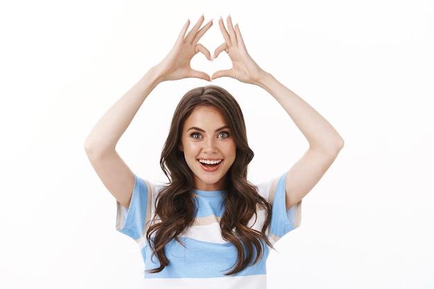 入れ墨のあるウエストアップのかわいい優しい現代の魅力的な女性は驚いて興奮しているように見えます頭の上に手を上げて心を示し、愛のジェスチャーは新しい店を崇拝し、同情を告白します