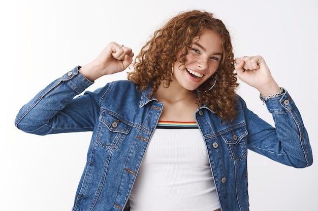 にきびが発生しやすい肌のそばかすのある20代の女の子の腰を上げて興奮した幸せな陽気な若い赤毛巻き毛のジャンプは、成功を祝って喜んで宝くじの達成目標を上げ、手を上げて勝利のジェスチャー、笑顔