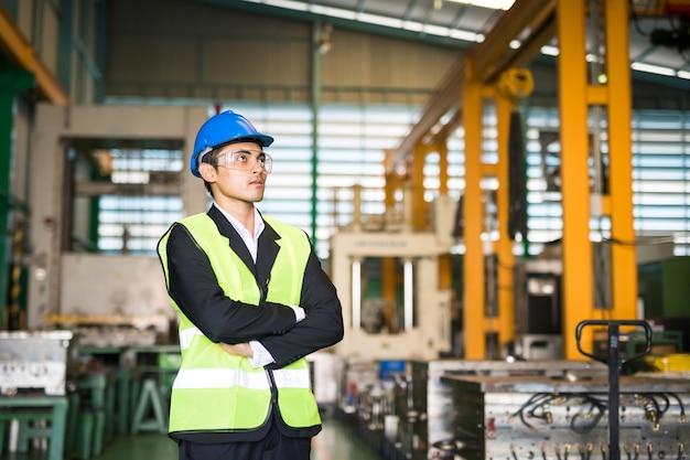 제조 창고의 재고 재고를 확인하기 위해 생산 부서에서 파란색 안전모를 쓴 공장 관리자를 허리에 올려 놓습니다. 산업 비즈니스 개념입니다.
