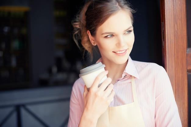 Waist up of female bartender having coffee
