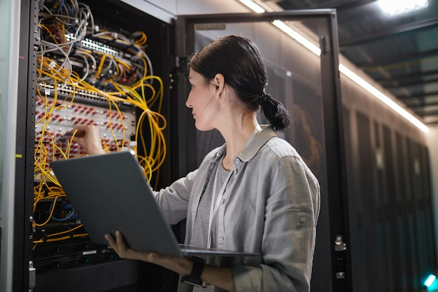 Waist up of female network engineer connecting cables in server cabinet while working with supercomputer in data center, copy space