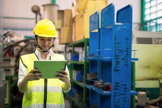 Подняв талию, работница проверяет товарные запасы на заводском складе с помощью приложения компании на цифровом планшете. обрабатывающая промышленность и технологии. промышленность с концепцией инвентаря.