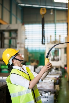 허리를 굽힌 여성 노동자는 원격 제어 패널을 사용하여 공장 창고에 있는 동력 트롤리 크레인을 들어 올리거나 내립니다. 아시아 여성이 제조 시설에서 크레인 빔을 제어합니다. 세로 초상화.