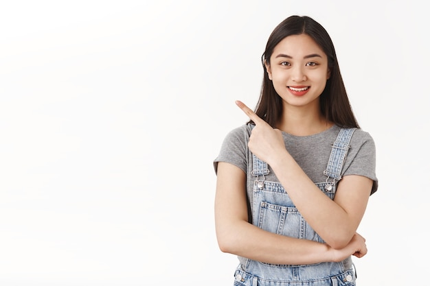 Waist-up friendly enthusiastic cute asian brunette girl explain cool place hang out show useful link pointing upper left corner smile recommend awesome product treat acne prone skin white wall