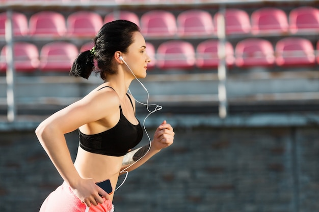 Waist up of girl running track on stadium and listening to music. profile of young woman in black top and pink shorts holding phone. outdoors, sport, closeup
