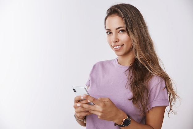Waist-up gorgeous smiling happy girl holding smartphone looking delighted tender camera, thinking capture under selfie posting photo social network, asking you take shot white wall