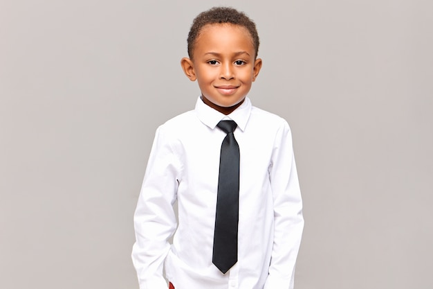 Waist up  handsome neat dark skinned male elementary pupil posing isolated dressed in white clean ironed shirt and black elegant tie, ready for going to school, smiling