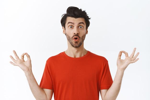 Красивый молодой современный парень с приподнятой талией, щетиной, небрежной прической, в красной футболке, держится за руки боком в позе лотоса, медитирует, занимается йогой, складывает губы в камеру с удивленным взглядом, белая стена